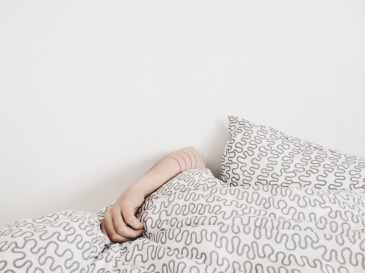 Against a cream-coloured wall, there is a similarly-toned pile of blankets and pillows, and a single forearm from somewhere underneath resting on top of the covers.