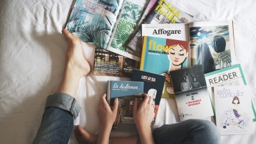 On a top-down view of a bed is an assortment of magazines and books, with a person's foot and hands visible in the frame.